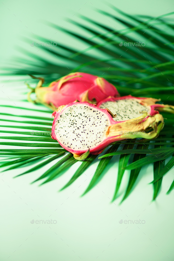 Pitahaya or dragon fruit over tropical green palm leaves on turquoise background. Copy space. Pop - Stock Photo - Images