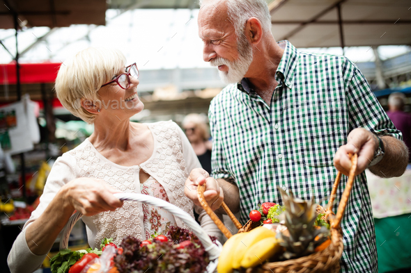Portrait of beautiful elderly couple in market buing food - Stock Photo - Images