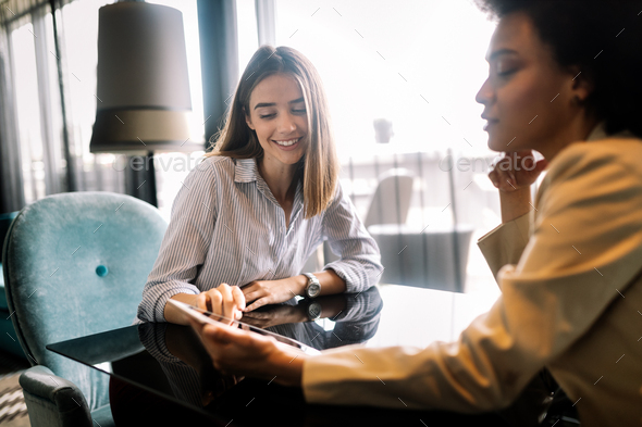 Successful attractive women friends chatting in cafe during coffee break - Stock Photo - Images