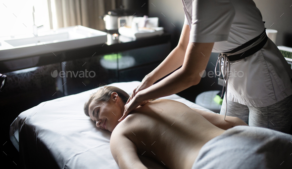 Beautiful young woman relaxing with massage treatment at beauty spa - Stock Photo - Images