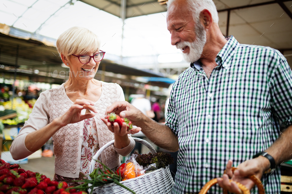 Mature shopping couple with basket on the market. Healthy diet - Stock Photo - Images