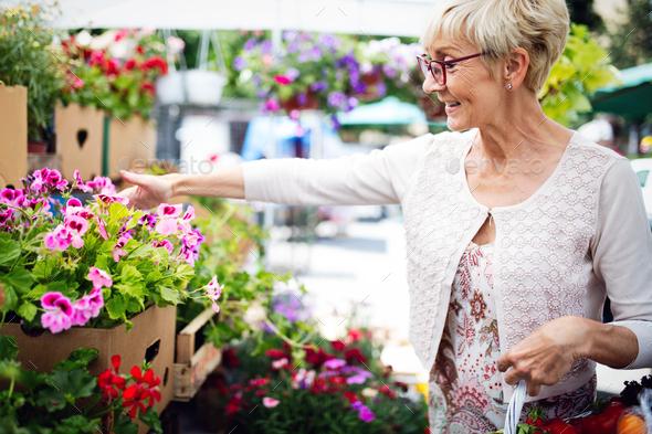 Beautiful senior woman selecting flowers at market - Stock Photo - Images