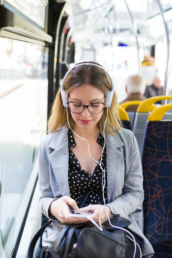 Pretty young woman listening to music with mobile phone at the b - Stock Photo - Images