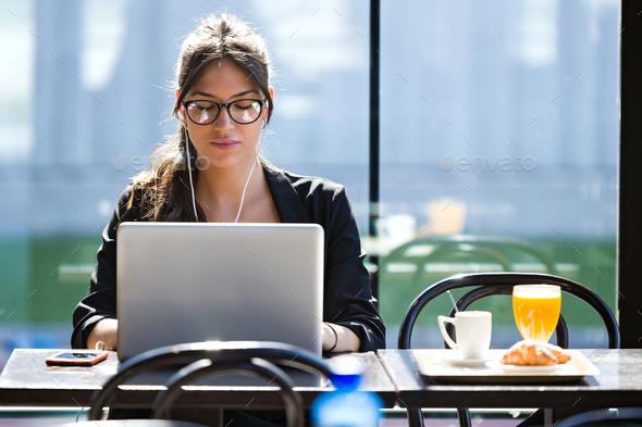 Beautiful young woman working with her laptop while having break - Stock Photo - Images