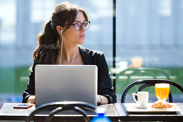 Beautiful young woman looking sideways while working with her la - Stock Photo - Images