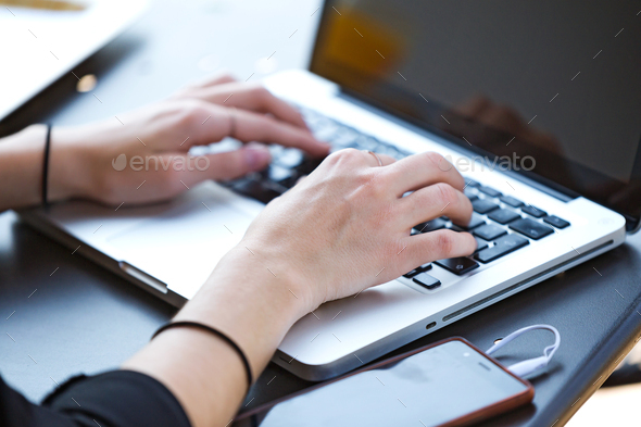 Young woman working with at laptop while loading the phone batte - Stock Photo - Images
