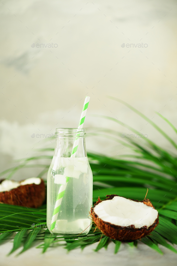 Bottle of coconut water and fresh ripe fruits on grey concrete background. Summer food concept - Stock Photo - Images
