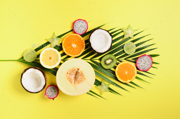 Exotic fruits and tropical palm leaves on pastel yellow background - papaya, mango, pineapple - Stock Photo - Images