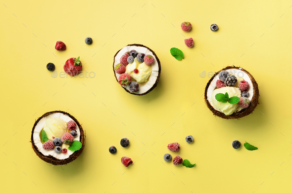 Coconut ice cream with fresh berries in coconuts halves on yellow background with copy space. Top - Stock Photo - Images