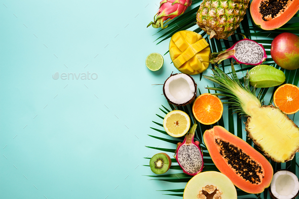 Exotic fruits and tropical palm leaves on pastel turquoise background - papaya, mango, pineapple - Stock Photo - Images