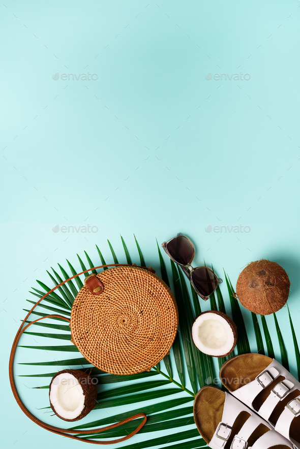 Round rattan bag, coconut, birkenstocks, palm branches, sunglasses on blue background. Banner. Top - Stock Photo - Images