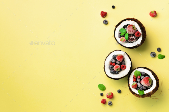 Fresh organic berries, mint leaves inside ripe coconuts on yellow background with copy space. Top - Stock Photo - Images