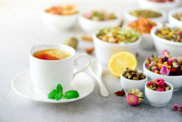 Tea concept with copy space. Different kinds of dry tea in white ceramic bowls and cup of aromatic - Stock Photo - Images