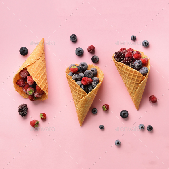Frozen berries - strawberry, blueberry, blackberry, raspberry in waffle cones on pink background - Stock Photo - Images