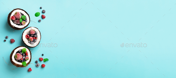 Fresh organic berries, mint leaves inside ripe coconuts on blue background with copy space. Top View - Stock Photo - Images