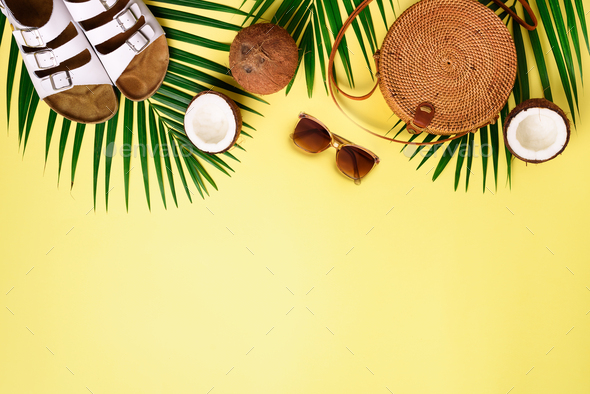 Round rattan bag, coconut, birkenstocks, palm branches, sunglasses on yellow background. Banner. Top - Stock Photo - Images