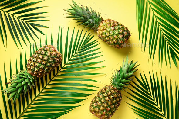 Pineapple and tropical palm leaves on yellow background. Top view. Summer concept. Creative flat lay - Stock Photo - Images