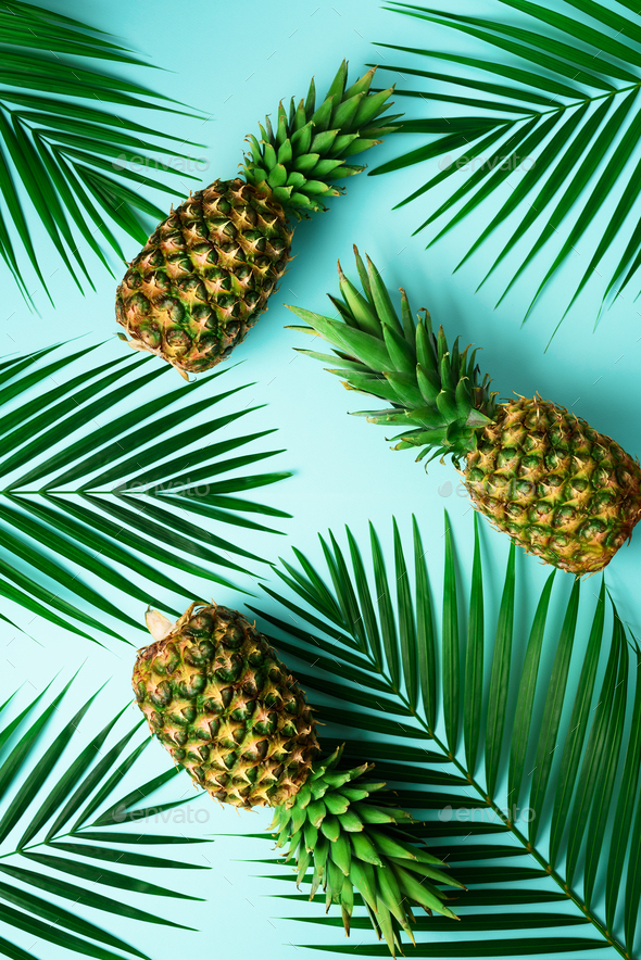 Pineapples and tropical palm leaves on pastel turquoise background. Summer concept. Creative flat - Stock Photo - Images