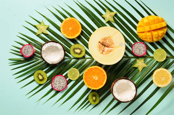 Exotic fruits and tropical palm leaves on pastel turquoise background - papaya, mango, pineapple - Stock Photo - Images