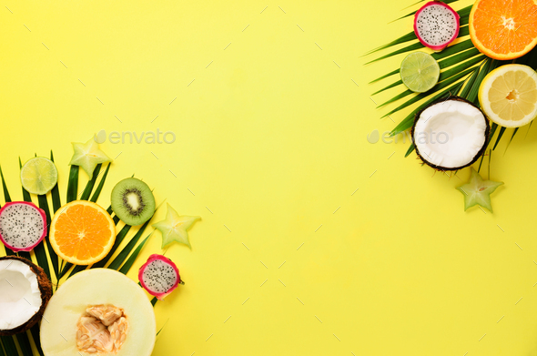 Exotic fruits and tropical palm leaves on pastel yellow background - papaya, mango, pineapple - Stock Photo - Images
