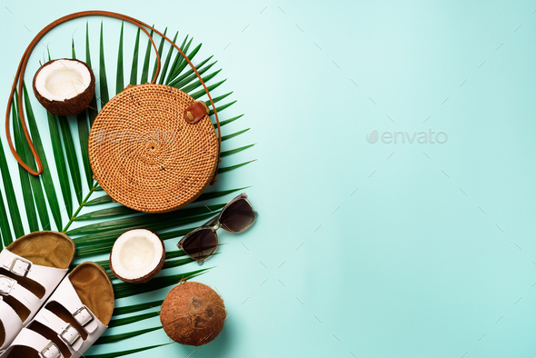 Stylish rattan bag, coconut, birkenstocks, palm branches, sunglasses on blue background. Banner. Top - Stock Photo - Images