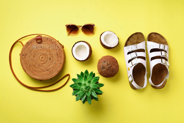 Stylish rattan bag, coconut, birkenstocks, palm branches, succulent, sunglasses on yellow background - Stock Photo - Images