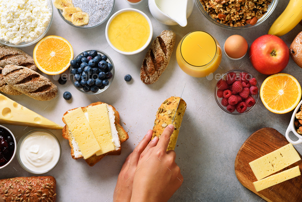 Female hands spreading butter on bread. Woman cooking breakfast. Healthy breakfast ingredients, food - Stock Photo - Images