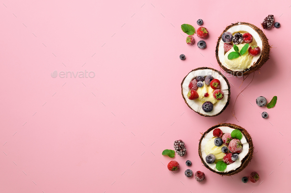 Coconut ice cream with fresh berries in coconuts halves on pink background with copy space. Top View - Stock Photo - Images