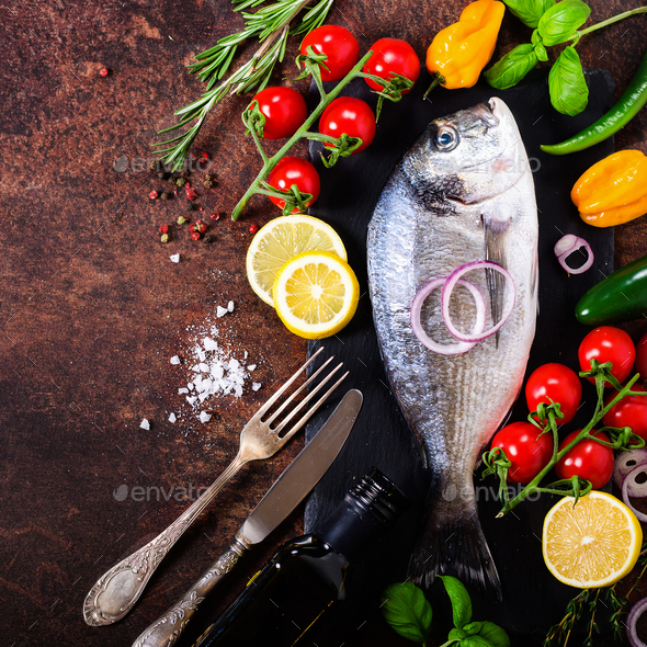 Fresh uncooked fish, dorado, sea bream with lemon, herbs, vegetables and spices on rustic background - Stock Photo - Images