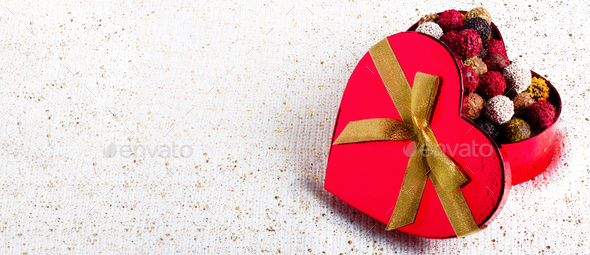 Handmade chocolate candies in red heart shape box with gold bowknot. Copy space. Banner - Stock Photo - Images