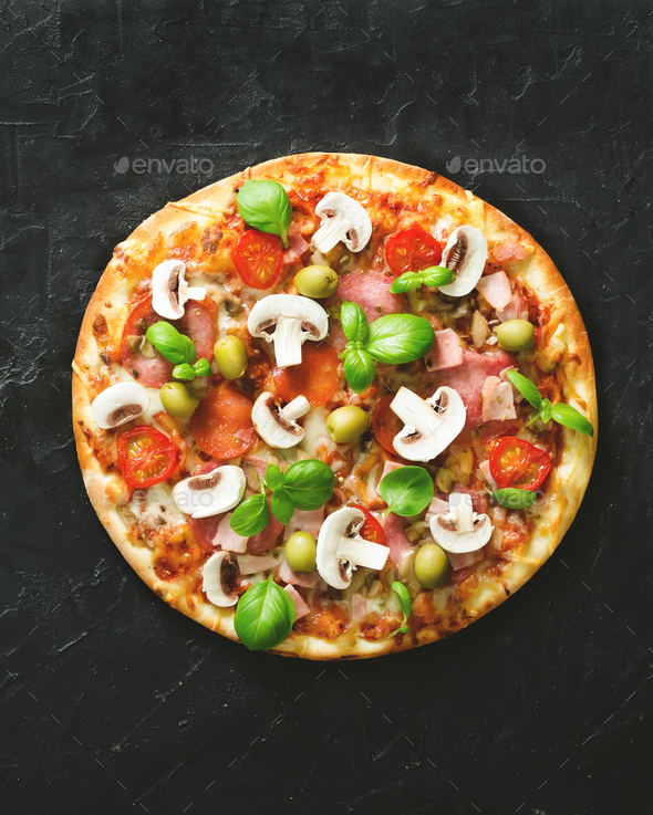 Fresh italian pizza with mushrooms, ham, tomatoes, cheese, olive, basil on black concrete background - Stock Photo - Images
