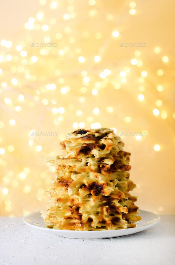 Traditional cake Shakotis, Sakotis on white plate, festive background, light new year and christmas - Stock Photo - Images