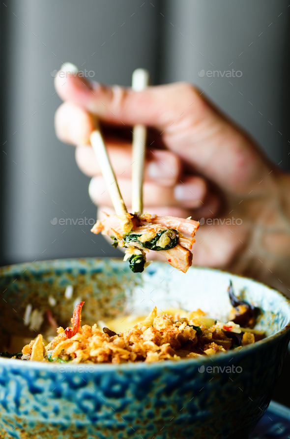 Man's hand holding chopsticks over a plate of Japanese, thai, chinese meal - rice, mushroom - Stock Photo - Images