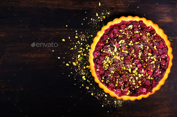Sweet tart with raspberries, cherries, red currants with pistachios, powdered sugar on dark wooden - Stock Photo - Images