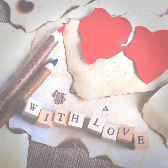 Old vintage sheet of paper, two red hearts, wooden pencils and words With love on cubes on burlap - Stock Photo - Images