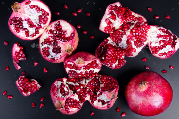 Broken pomegranate and grains on black background. Copy space - Stock Photo - Images