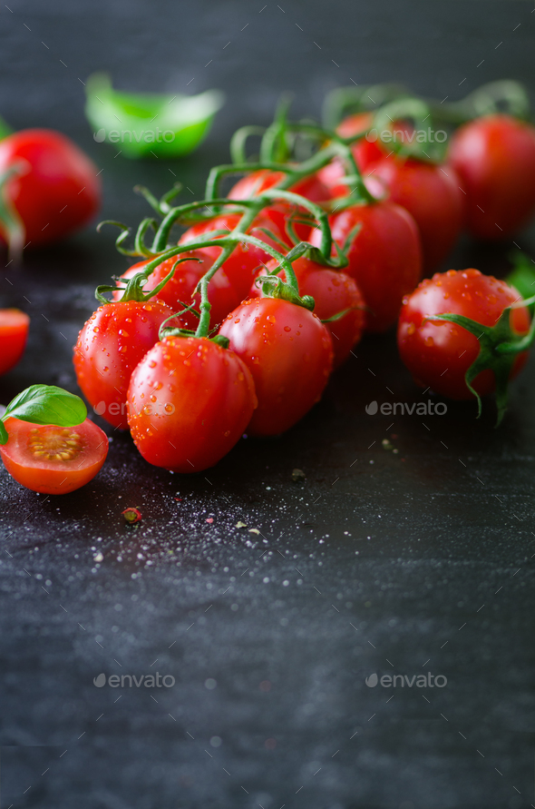 Fresh cherry tomatoes on black background with basil, spices. Copy space - Stock Photo - Images