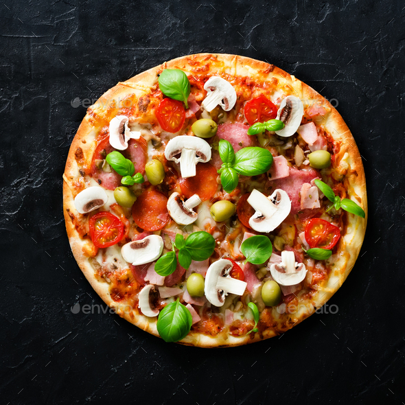 Fresh italian pizza with mushrooms, ham, tomatoes, cheese on on black concrete background. Copy - Stock Photo - Images