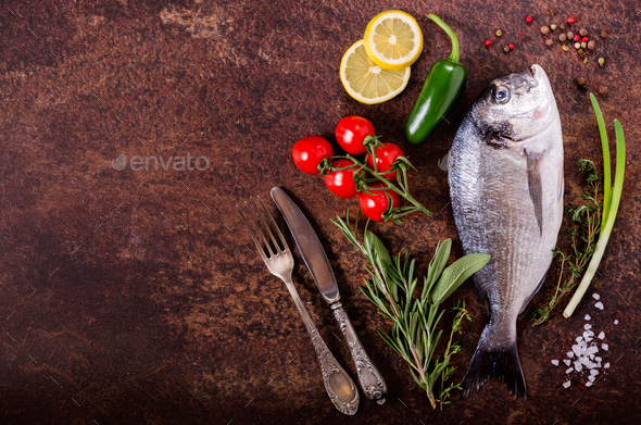 Fresh raw fish with lemon, herbs, onion, paprika, cherry tomatoes, onion, salt on rustic background - Stock Photo - Images