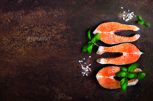 Raw fresh salmon fillet with aromatic herbs, spices, salt and lemon on wooden background. Healthy - Stock Photo - Images