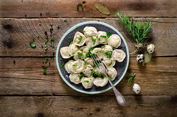 Traditional russian pelmeni, ravioli, dumplings with meat on wooden table with flour, parsley, quail - Stock Photo - Images