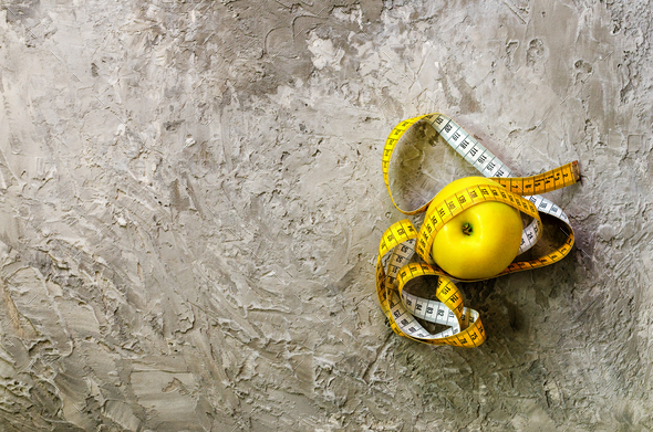 Yellow apple with measuring tape on concrete background. Top view - Stock Photo - Images