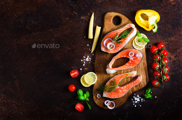 Raw salmon steaks, aromatic herbs, onion, lemon, salt and fresh vegetables for cooking on wooden - Stock Photo - Images