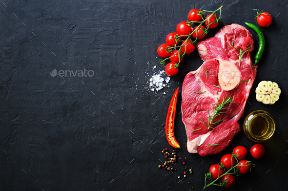 Raw meat steaks with cherry tomatoes, hot pepper, garlic, oil and herbs on dark stone, concrete - Stock Photo - Images