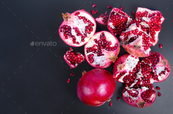 Ripe juice pomegranate fruit on black background - whole and cut, top view - Stock Photo - Images