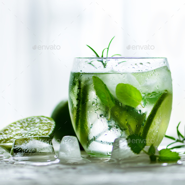 Homemade lime lemonade with cucumber, rosemary and ice, white background. Cold beverage for hot - Stock Photo - Images