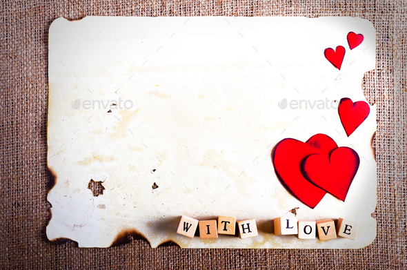 Old vintage sheet of paper, two red hearts, words With love on cubes on burlap, sackcloth background - Stock Photo - Images