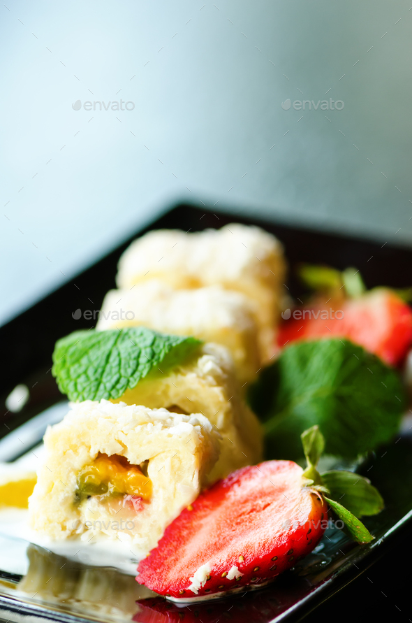 White sweet roll with kiwi, peaches, strawberries, mint. Serverd with almond peach and chocolate - Stock Photo - Images