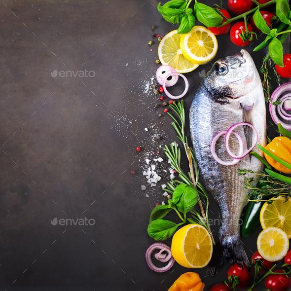 Dorada, fresh fish with vegetable, lemon, herbs, onion, paprika, cherry tomatoes, onion, salton dark - Stock Photo - Images
