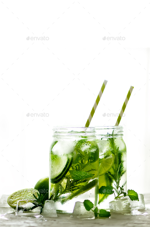 Cold and refreshing detox water with lime, cucumber, rosemary and ice in glass jar. Copyspace - Stock Photo - Images